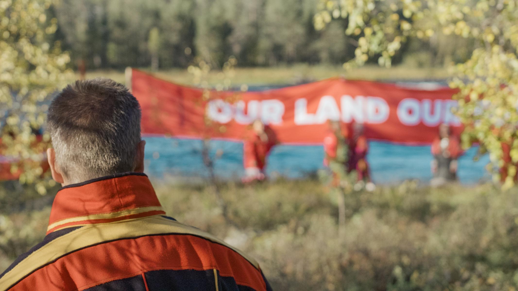 """Aktivisteja Red line -mielenilmauksessa Inarissa. Taustalla banderolli, jossa lukee """"Our land""""."""