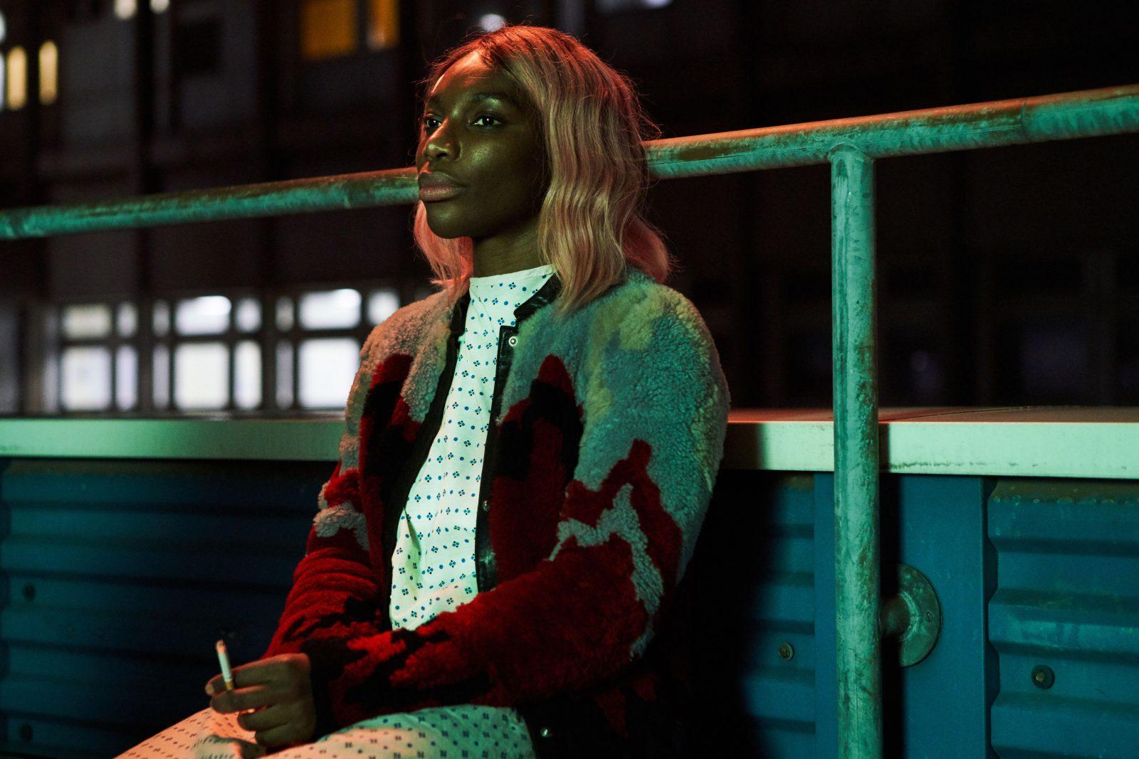Ilmeetön Arabella polttaa tupakkaa vihreässä valossa.