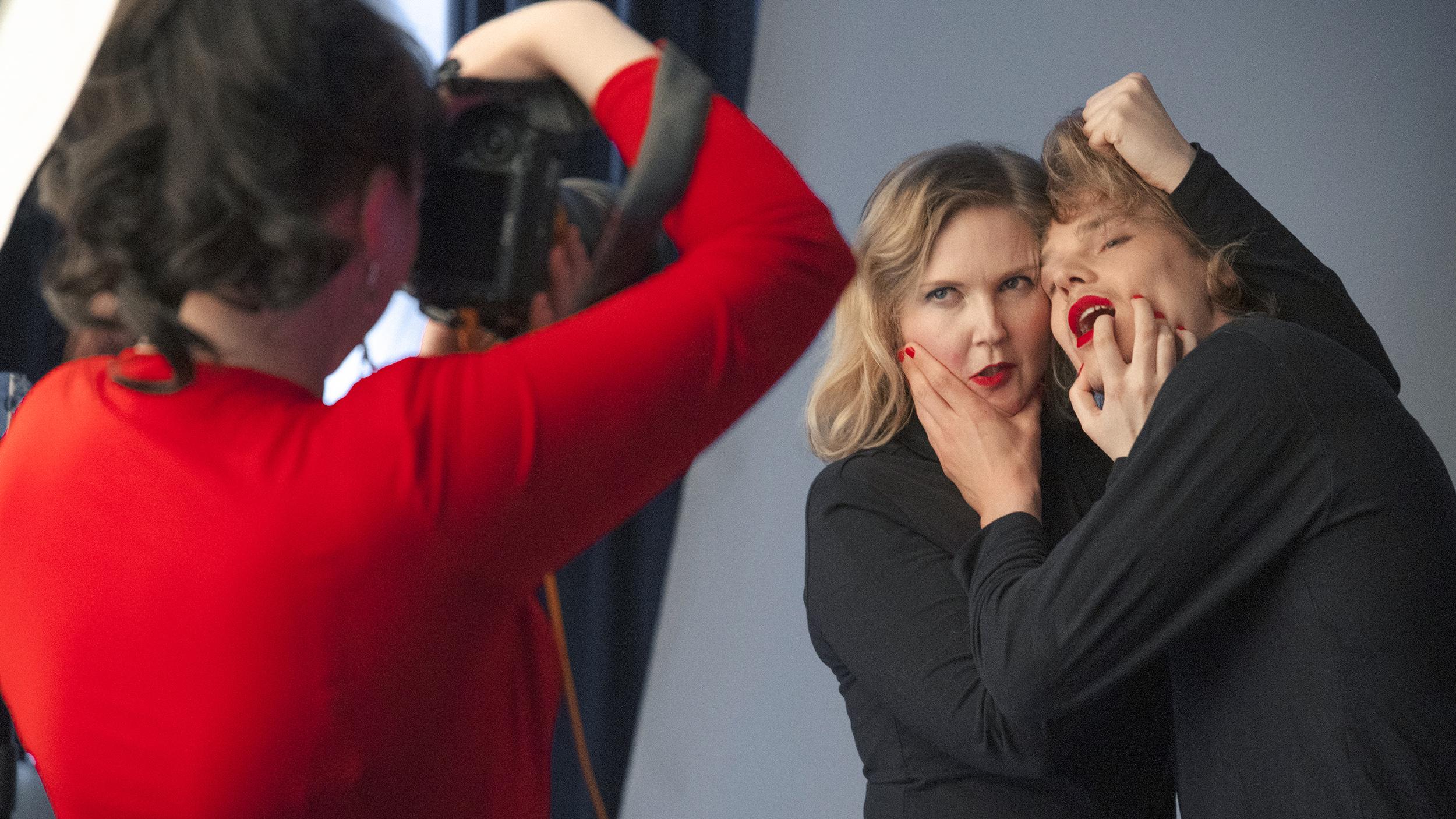 Punapaitainen henkilö valokuvaa mustiin pukeutunutta pariskuntaa, joilla on molemmilla punaista huulipunaa ja kynsilakkaa.